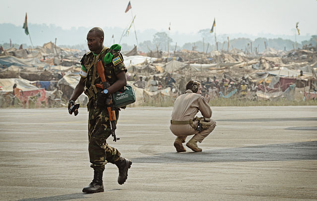 A Rwandan soldier, left, exits a U.S. Air Force C-17 Globemaster III aircraft near a refugee camp full of displaced residents at Bangui M'Poko International Airport. Photo by SSgt Ryan Crane (public domain)